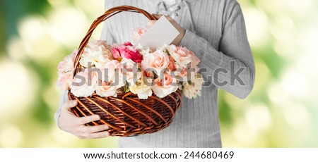 holidays, people, feelings and greetings concept - close up of man holding basket full of flowers and postcard over green background - stock photo