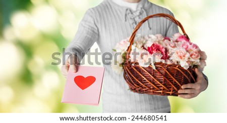 holidays, people, feelings and greetings concept - close up of man holding basket full of flowers and giving postcard over green background - stock photo