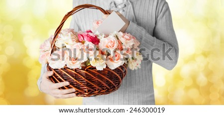 holidays, people, feelings and greetings concept - close up of man holding basket full of flowers and postcard over yellow lights background - stock photo