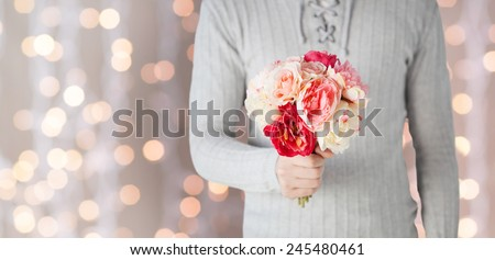 holidays, people, feelings and greetings concept - close up of man holding bunch of flowers over lights background - stock photo