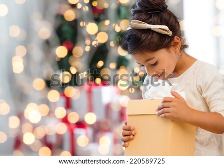 holidays, presents, childhood and people concept - smiling little girl with gift box over living room and christmas thee background - stock photo