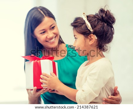holidays, presents, christmas,  birthday concept - happy mother and child girl with gift box - stock photo