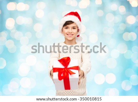 holidays, presents, christmas, childhood and people concept - smiling happy boy in santa hat with gift box over blue lights background - stock photo