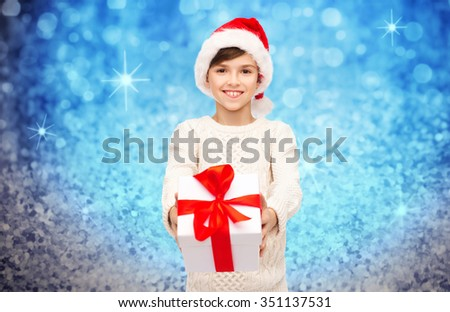 holidays, presents, christmas, childhood and people concept - smiling happy boy in santa hat with gift box over blue lights or glitter background - stock photo