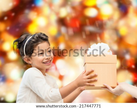 holidays, presents, christmas, childhood and people concept - smiling little girl with gift box over red lights background - stock photo
