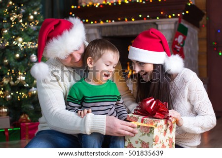holidays, presents, christmas concept - happy mother, father and kid boy with gift box