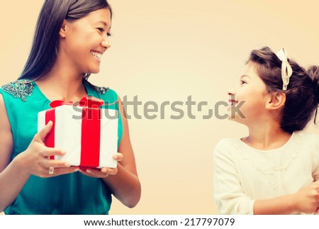 holidays, presents, family, christmas and x-mas concept - happy mother and child girl with gift box - stock photo