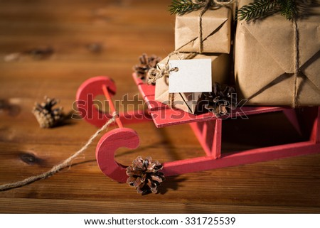 holidays, presents, new year and celebration concept - close up of gift boxes with blank note on red wooden sleigh and pinecones - stock photo