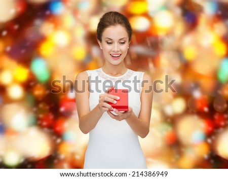 holidays, presents, wedding and happiness concept - smiling woman in white dress holding red gift box over party lights background - stock photo