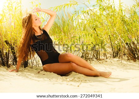 Holidays, summer and beauty concept. Sensual girl in black swimwear posing on sandy beach, grassy dunes. Pretty woman on the sea coast.