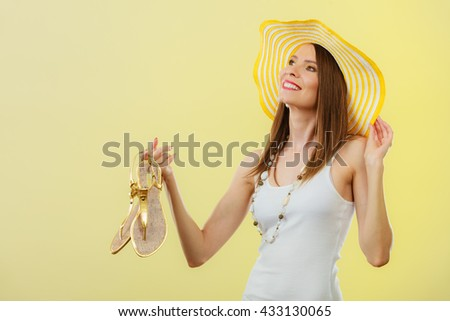 Holidays summer fashion concept. Woman in big yellow hat holding golden sandals in hand bright background.
