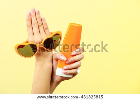 Holidays summer fashion eyes protection and skin care concept. Woman holding in hand heart shaped sunglasses sunscreen lotion, yellow background - stock photo