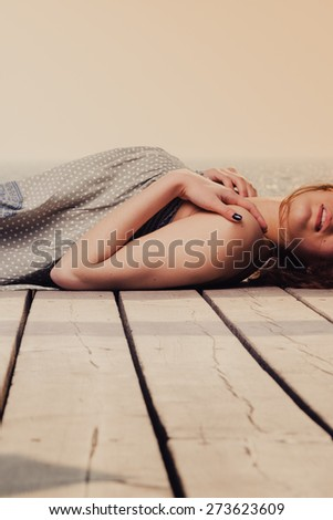 Holidays summer relaxation concept. Young woman relaxing on pier outdoor