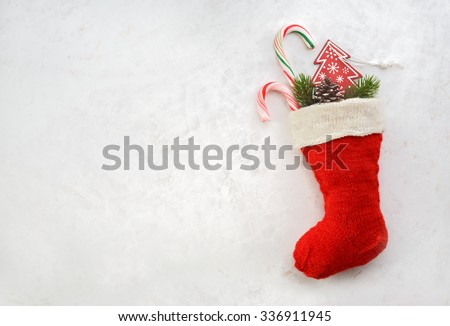 Holidays symbol stocking. Red christmas sock with gifts on a light background. Christmas background with copyspace - stock photo
