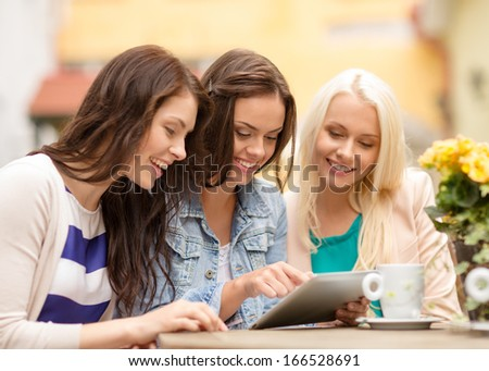 holidays, tourism, technology and internet - three beautiful girls looking at tablet pc computer in cafe outside - stock photo