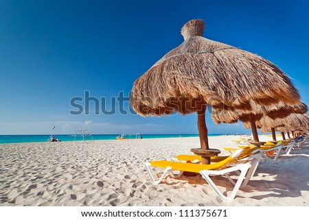 Holidays under parasol on Caribbean beach - stock photo