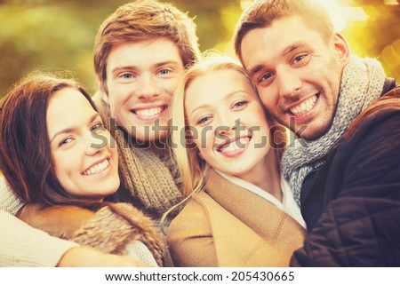 holidays, vacation, happy people concept - group of friends or couples having fun in autumn park - stock photo