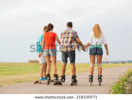 holidays, vacation, love and friendship concept - group of teenagers with roller skates and skateboard riding outdoors from back - stock photo