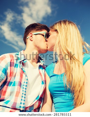 holidays, vacation, love and friendship concept - smiling couple kissing outdoors - stock photo