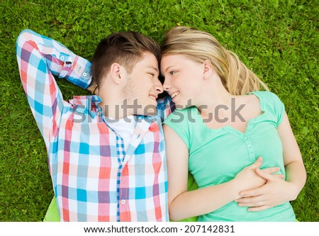 holidays, vacation, love and friendship concept - smiling couple lying on blanket in park - stock photo