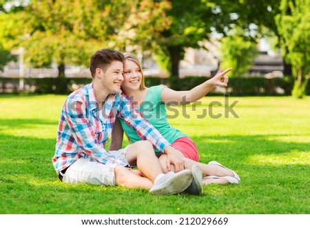 holidays, vacation, love and friendship concept - smiling couple sitting on grass and pointing finger in park - stock photo