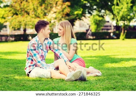 holidays, vacation, love and friendship concept - smiling couple sitting on grass and talking in park - stock photo