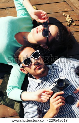 Holidays, vacation, love and friendship concept - smiling fashion couple having fun outdoors. Man with girl in spring urban style. Photo toned style Instagram filters. - stock photo