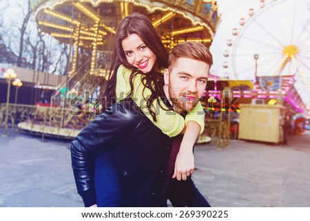 Holidays, vacation, love and friendship concept - smiling  stylish  couple having fun in  an amusement.  Young couple embracing laughing on date. Bright   colorful filter. - stock photo