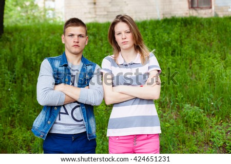 holidays, vacation, love and friendship concept - smiling teen couple young cheerful hipster Best Friends boy and girl having fun, played outdoors, mimic fight, positive, laid hands on stomach - stock photo