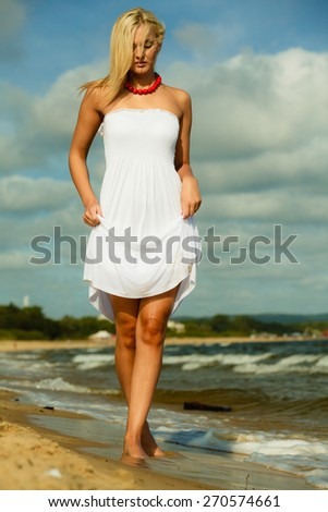 Holidays, vacation travel and freedom concept. Beautiful girl in white dress walking on beach. Young woman relaxing on the sea coast.
