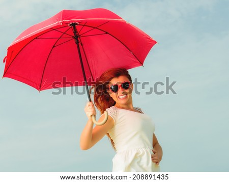 Holidays, vacation travel and freedom concept. Beautiful redhaired happy girl jumping with red umbrella on beach.