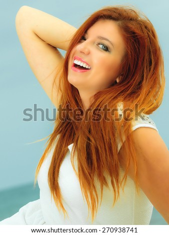 Holidays, vacation travel and freedom concept. Beautiful redhaired happy girl on beach, portrait