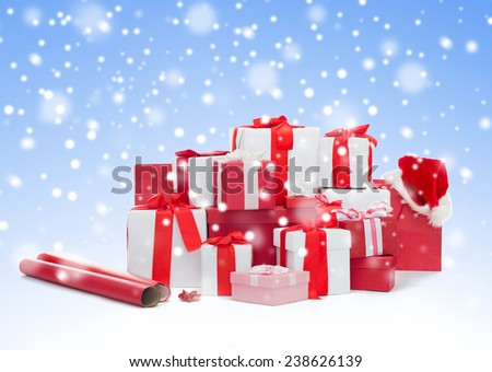 holidays, winter, birthday and celebration concept - christmas presents, decoration paper and santa helper hat over blue background with snow - stock photo