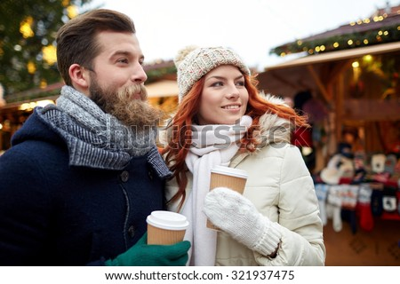 holidays, winter, christmas, hot drinks and people concept - happy couple of tourists in warm clothes drinking coffee from disposable paper cups in old town - stock photo