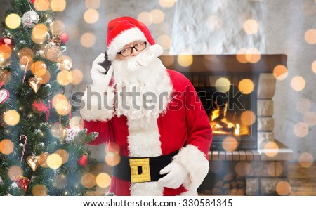 holidays, winter, technology and people concept - man in costume of santa claus calling on smartphone and christmas tree over home fireplace and lights background - stock photo