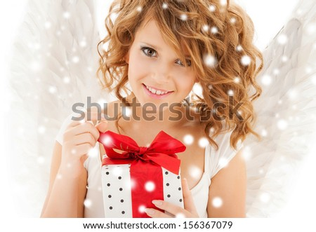 holidays, xmas and costumes concept - happy teenage angel girl with christmas gift - stock photo