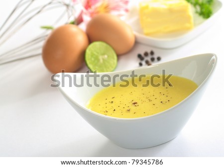 Hollandaise sauce with black pepper and the ingredients (butter, egg, lemon) of the sauce in the back (Selective Focus, Focus in the middle of the bowl)