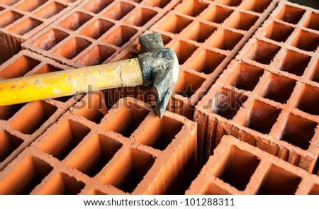 Hollow brick with an hammer on construction site - stock photo