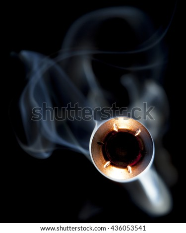 Hollow point bullet in copper and lead with smoke coming close - stock photo