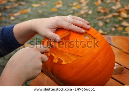 Hollowing out a pumpkin to prepare halloween lantern - stock photo