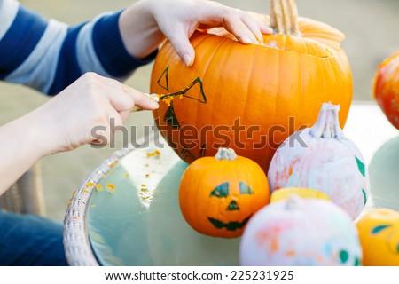 Hollowing out a pumpkin to prepare halloween lantern. Hands of man making jack-o-lantern. - stock photo