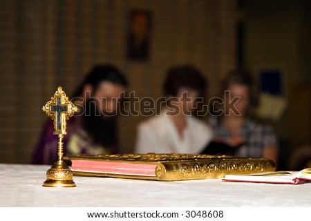 holly cross in the altar, religious book with gold covers, priest and followers - stock photo