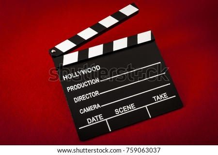 Hollywood And The Movie Industry Concept With A Vintage Clapper Board On Red Background