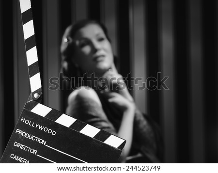 Hollywood black and white, a beautiful acting woman and a clapboard - minimal lighting and strong contrast - stock photo