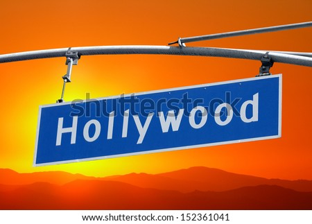 Hollywood Blvd street sign  and mountains with orange sunset sky. - stock photo