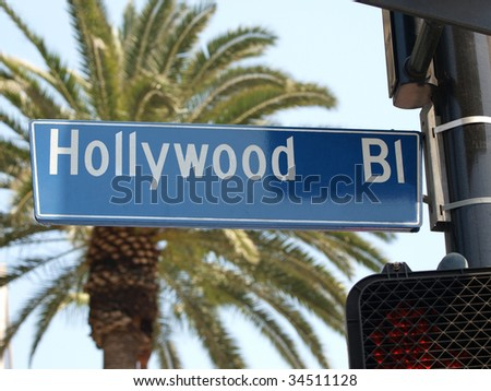 Hollywood Blvd street sign with large palm tree. - stock photo