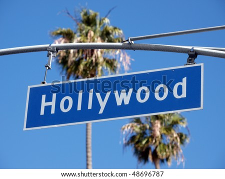 Hollywood Blvd street sign with tall palm trees. - stock photo