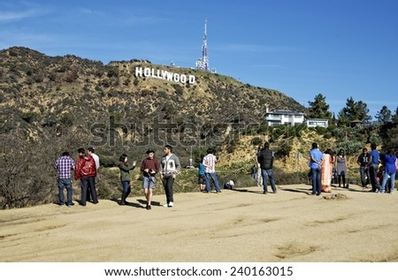 HOLLYWOOD, CALIFORNIA  DECEMBER 27: Tourists visiting the Hollywood Sign, built in 1923. This iconic landmark identifies The Entertainment Capital of the World, on December 27, 2014, in Hollywood. - stock photo