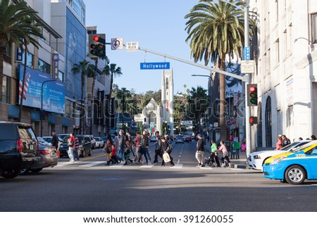 HOLLYWOOD, CALIFORNIA - February 8 2015: People crossing the street at an entersection on Hollywood Blvd  on February 8, 2015 in Hollywood, CA.