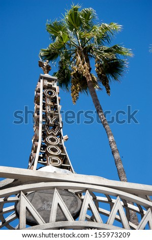 HOLLYWOOD - CALIFORNIA 26: The Hollywood Sign with a palm tree on its side, at the entrance of the Hollywood Walk of Fame in Hollywood, California, on September 26, 2013. - stock photo